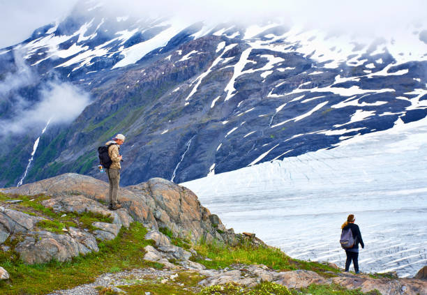 Tourists looking at the view. Closed clouds day, overlooking the Exit Glacier showing its blue ice, white snow, and a lush landscape. Exit Glacier in Kenai Fjords National Park, Alaska. July 27, 2018 stock photo