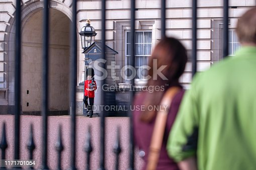 Tourists looking through the gates of Buckingham Palace at sentry of the Grenadier Guards standing in the late summer sunshine
