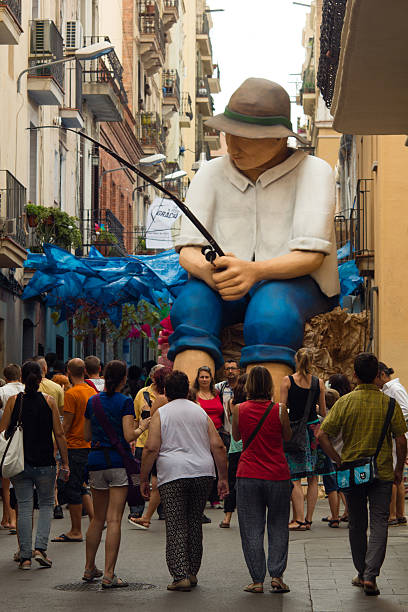 tourists make photos with giant sculpture of fisher man Barcelona, Spain - August 16, 2016: annual