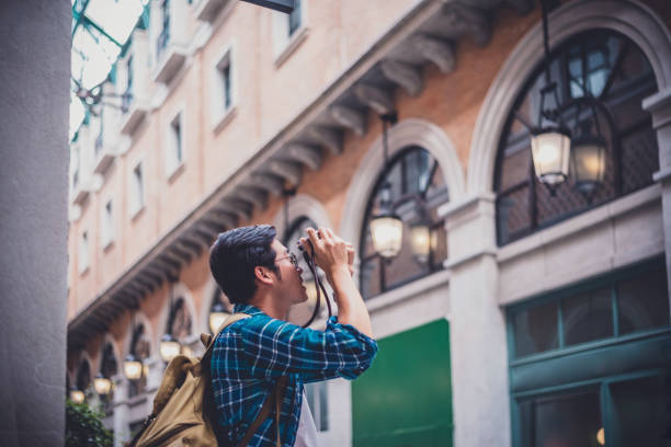 Tourists man with backpacks with camera travel photo of photographer on sightseeing city. travel and lifestyle concept. stock photo