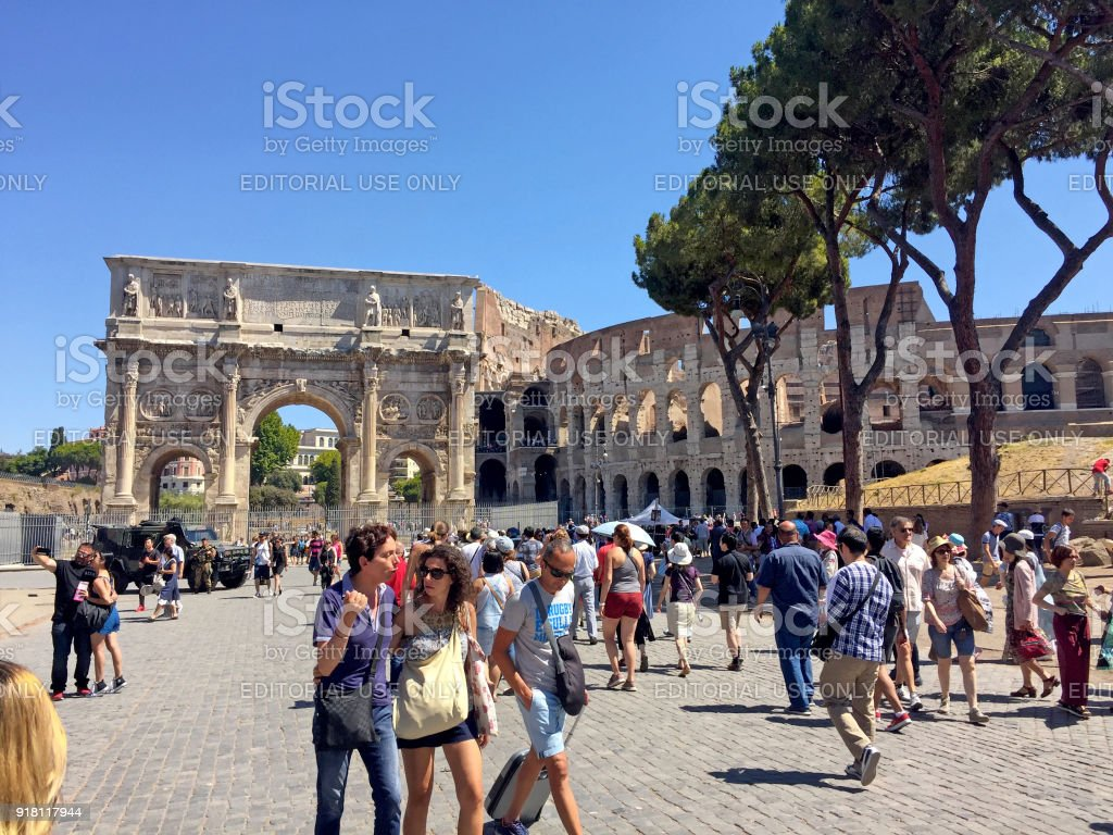 Tourists near Colosseum and Constantine arch in Rome, Italy. stock photo