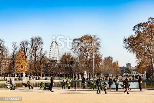 Paris, France - December 4, 2019: Tourists in front of the louvre and Ferris wheel on a bright sunny winters day in Tuileries Gardens.