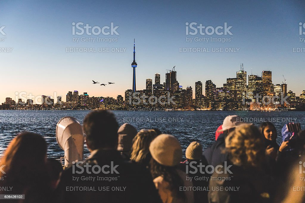 Tourists on a ferry boat in Toronto Toronto, Canada - October 13, 2016: People on the ferry boat from Toronto islands to downtown looking at the skyline and taking pictures with phones at sunset Architecture Stock Photo