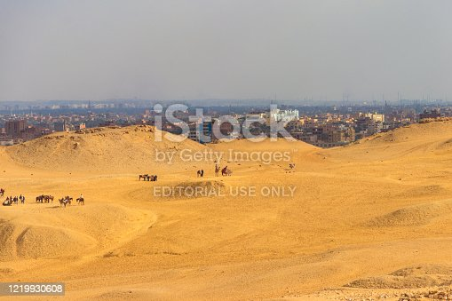 883177796 istock photo Tourists on a Giza plateau in Cairo, Egypt. Cityscape of Cairo on a background 1219930608