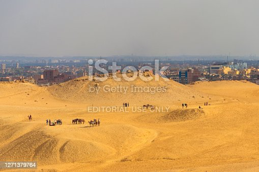 Cairo, Egypt - December 8, 2018: Tourists on a Giza plateau in Cairo, Egypt. Cityscape of Cairo on a background
