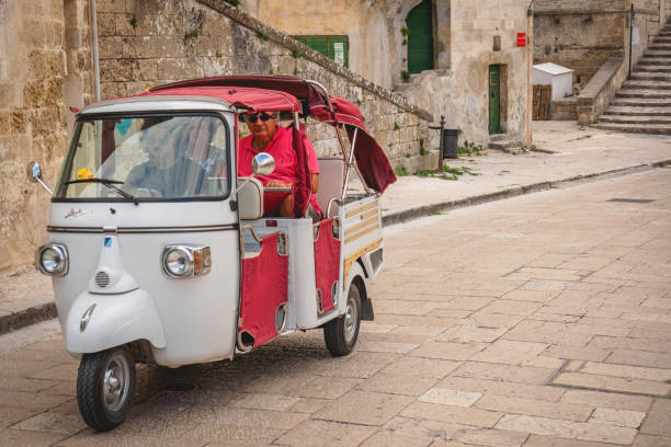 Tourists on a Piaggio Ape Calessino used as a taxi. Matera, Italy - September, 2017. Tourists on a Piaggio Ape Calessino used as a taxi. Landscape format. matera italy stock pictures, royalty-free photos & images