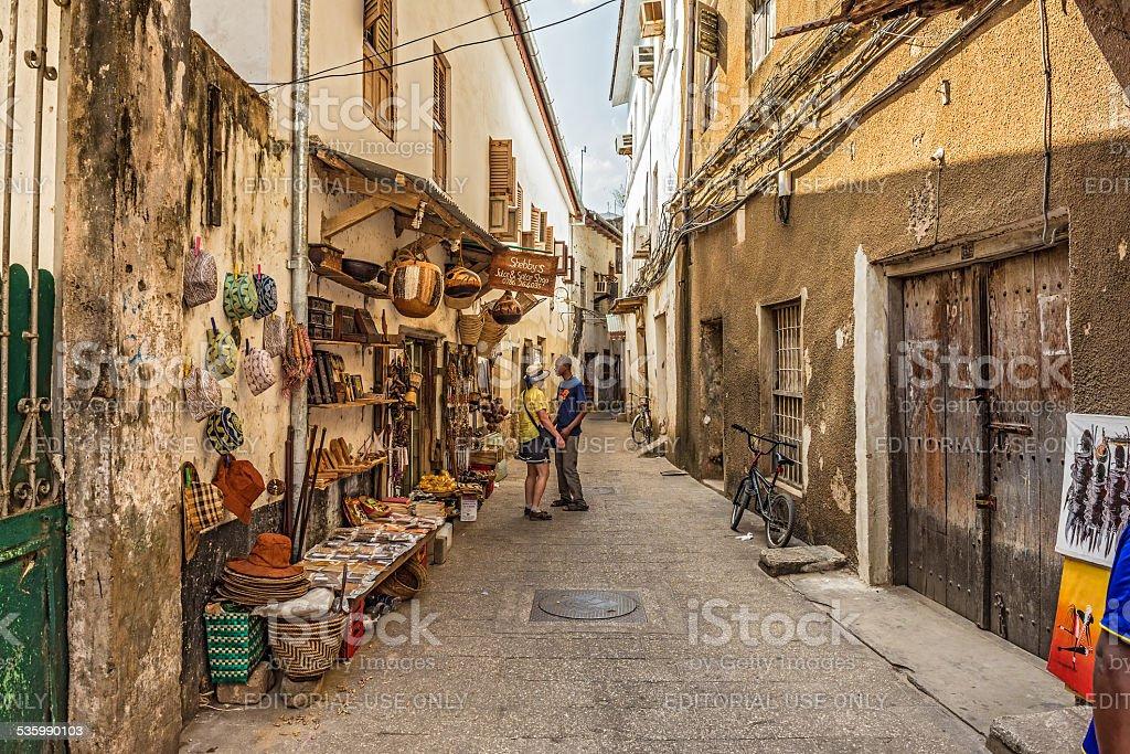 Tourists on a typical narrow street in Stone Town, Zanzibar stock photo