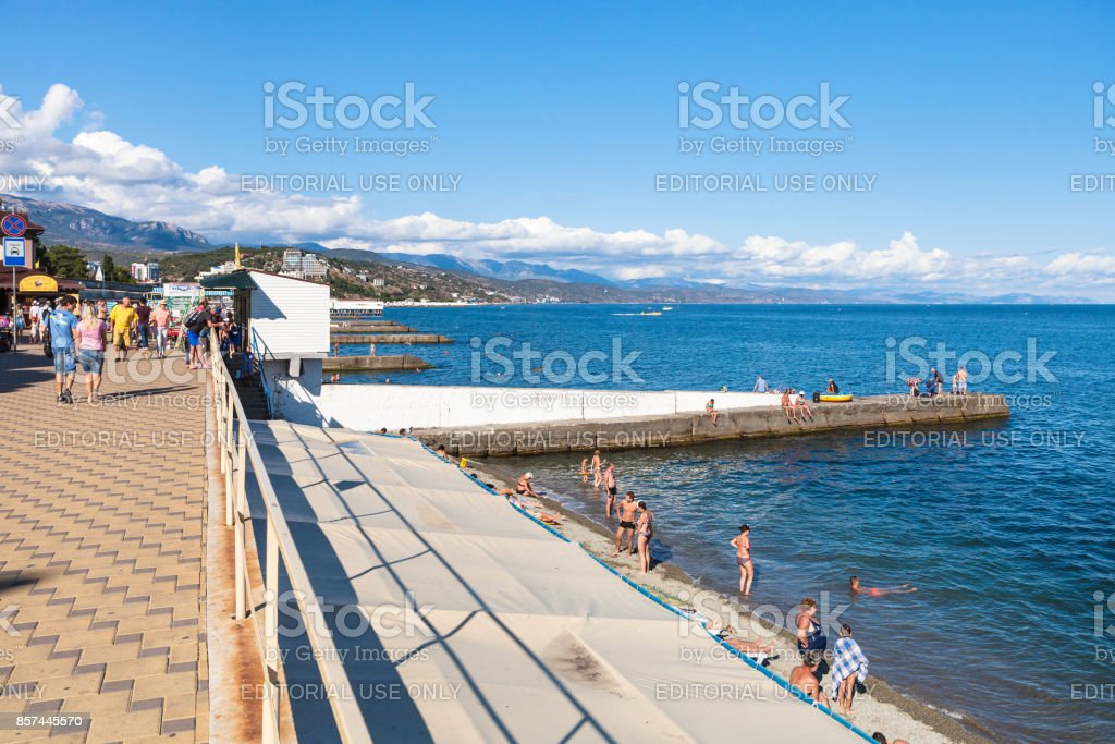tourists on beach along embankment in Alushta stock photo