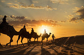 Tourists riding camels at sunset on the dunes of the Abi Dhabi Empty Quarter Desert