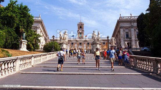 Rome, Italy - August 31, 2017: Tourists on Michelangelo stairs to Piazza del Campidoglio on top of Capitoline Hill and Palazzo Senatorio, Rome, Italy.