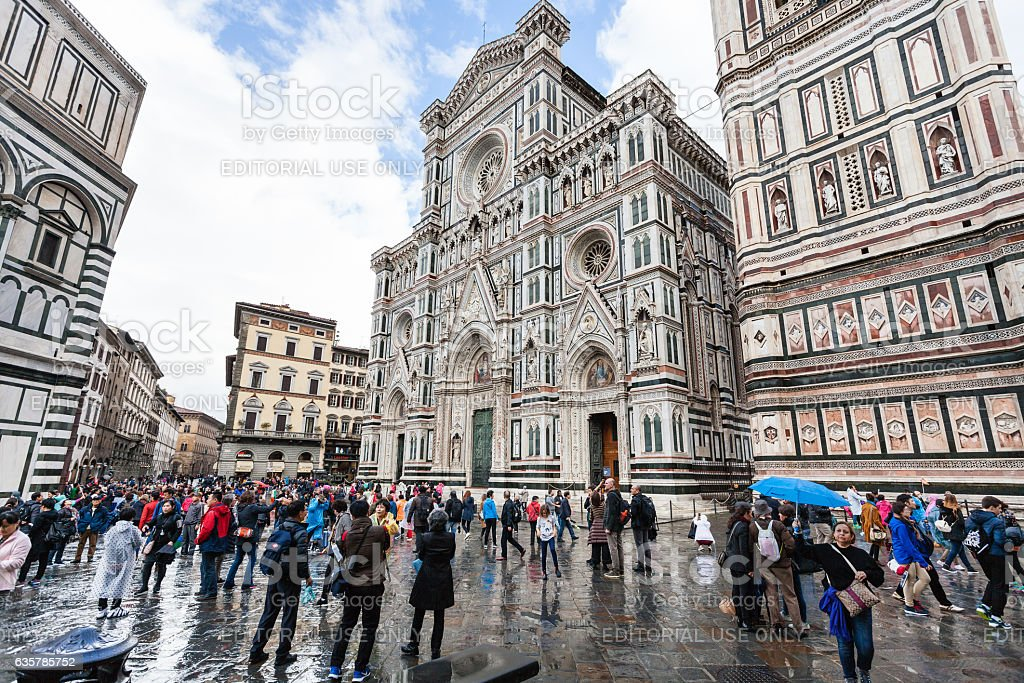 tourists on piazza san giovanni near Duomo in rain stock photo