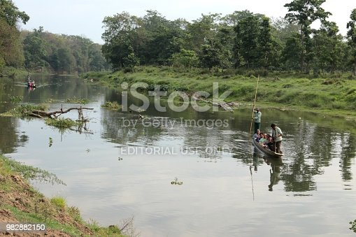 Chitwan, Nepal, May 2018: Tourists on a rowboat going on a tour on a Rapti river in Chitwan national park. Tourists could see crocodiles, birds and variouse wild animals.