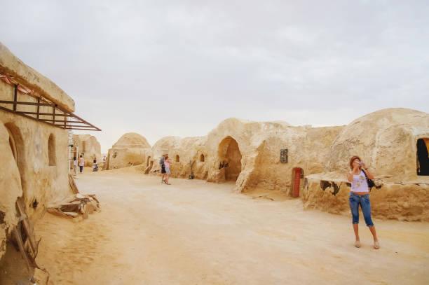 """touristen auf kulisse für den film """"star wars"""" in der nähe von nefta stadt in tunesien. planeten tatooine industrieanlagen. - urlaub in tunesien stock-fotos und bilder"""
