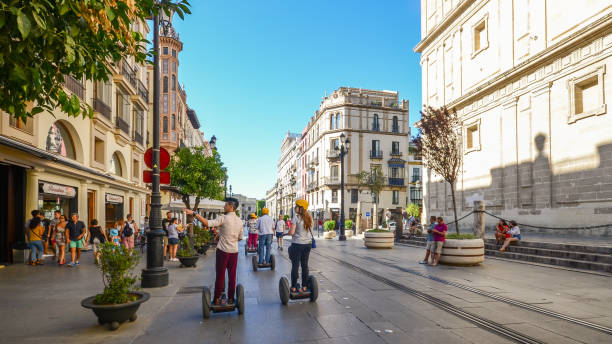 Tourists on segways at Av. de la Constitucion in the historic centre of Seville, Andalusia, Spain Tourists at Av. de la Constitucion in the historic centre of Seville, Andalusia, Spain santa cruz seville stock pictures, royalty-free photos & images