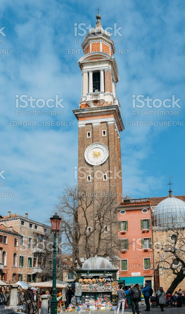 Tourists on square Campo Santi Apostoli and view of clock tower of the Church of the Holy Apostles of Christ, San Apostoli in Venice stock photo