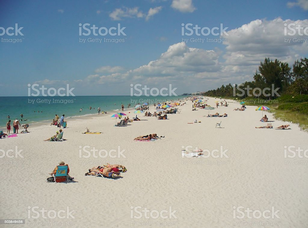 Tourists on the beach and in the water stock photo