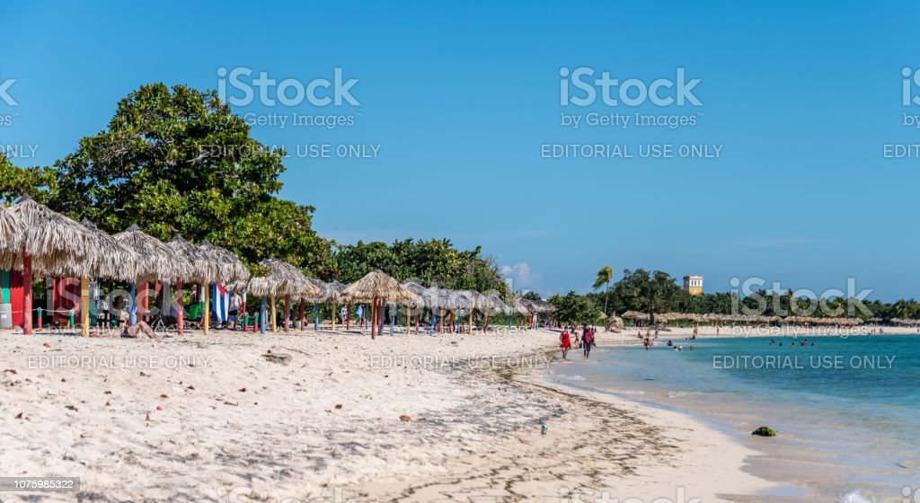 Tourists on the beach at Playa Ancón in Cuba stock photo