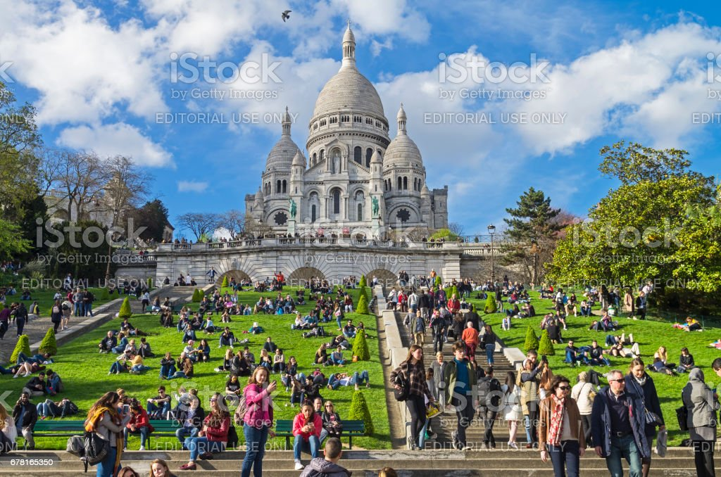 Tourists on the hillside of Montmartre on the background of the Sacre-Coeur basilica. stock photo
