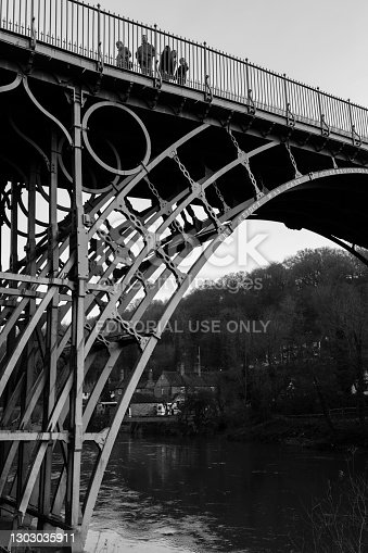 Telford, UK - February 18, 2013. A group of tourists cross The Iron Bridge, the first cast iron arch bridge built over Ironbridge Gorge at the start of the industrial revolution. Monochrome image.
