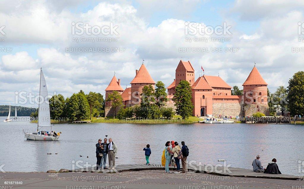 Tourists on the lake coast with Trakai Castle, Lithuania stock photo