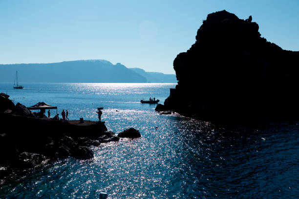 Tourists on the rocks and boats near Amoudi Bay on Santorini Island in Greece stock photo