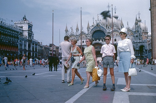 Venice, Veneto, Italy, 1969. Tourists in St. Mark's Square in Venice. Also: St. Marcus Cathedral, pigeons and Renaissance buildings.