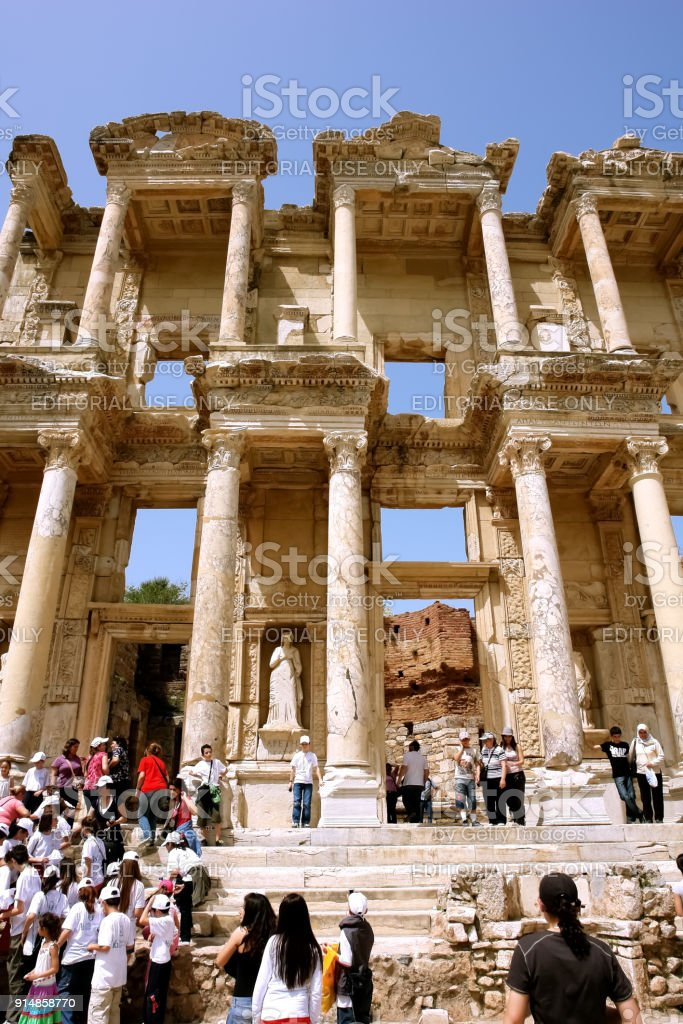 Tourists on the steps of the ruins of the ancient Roman library of Celsus in the ancient city of Ephesus. stock photo