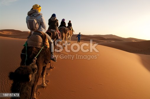 istock Tourists on train of camels in Sahara led by guide 155157473