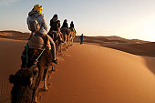 Anonymous guide leads camels with tourists riding into setting sun in Sahara desert.