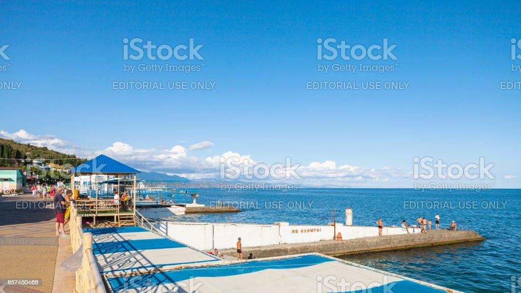 tourists on urban beach along embankment stock photo