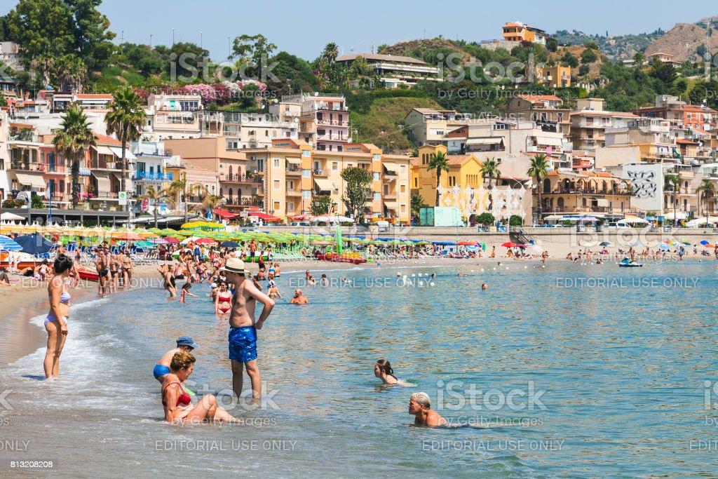 tourists on urban beach in Giardini Naxos city stock photo