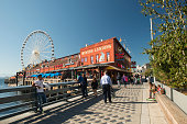 Seattle, USA - September 27, 2017. Tourists on waterfront walk at Pier 57 on Alaskan Way in downtown Seattle with view of Miners Landing food court building and Ferris Wheel (Seattle Great Wheel), Washington State.