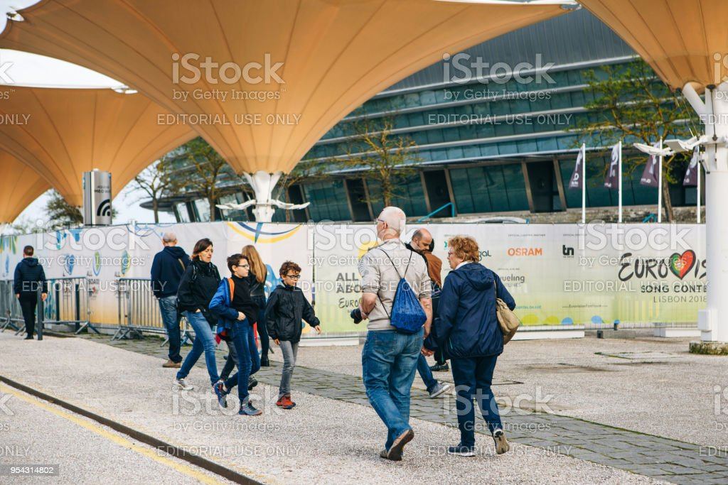 Tourists or company of friends or group of people or pedestrians or passersby walk down by street stock photo