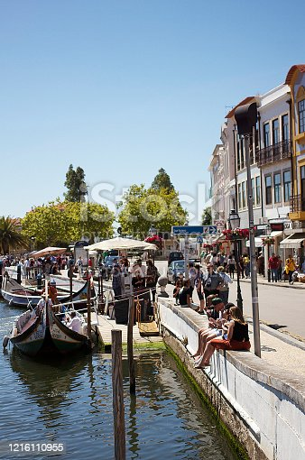 Aveiro, Portugal - June 15, 2019: View of tourists by the canal, boats, colourful houses, local businesses, locals and visitors, in Aveiro, Portugal.