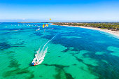 Tourists parasailing near Bavaro Beach, Punta Cana in Dominican Republic. Aerial view of tropical resort.
