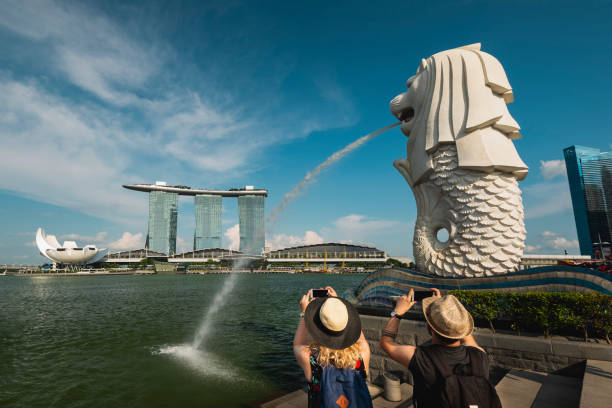 Tourists photographing Merlion Park and Marina Bay Sands at Marina Bay, Singapore Tourists taking picture of Singapore Merlion and Marina Bay Sands Hotel merlion fictional character stock pictures, royalty-free photos & images
