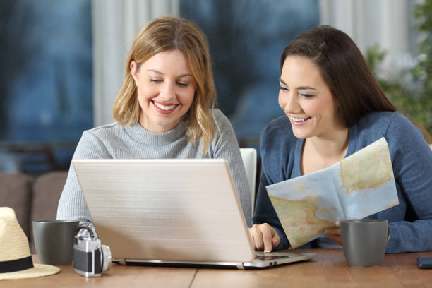 Tourists planning travel in an apartment Front view portrait of two happy tourists planning travel in an apartment making a reservation stock pictures, royalty-free photos & images
