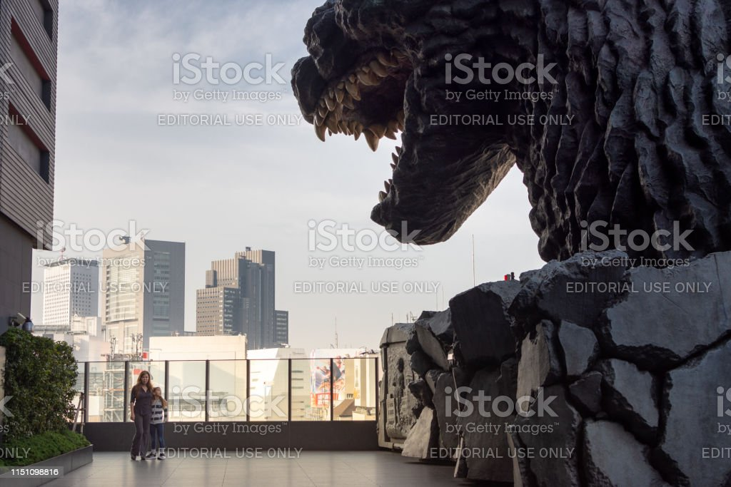 Tourists pose next to Godzilla on Hotel Gracery terrace in Tokyo, Japan - Royalty-free 8-9 Years Stock Photo