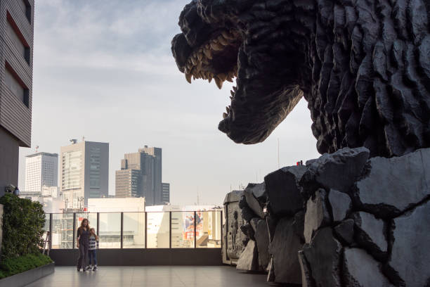 Tourists pose next to Godzilla on Hotel Gracery terrace in Tokyo, Japan stock photo