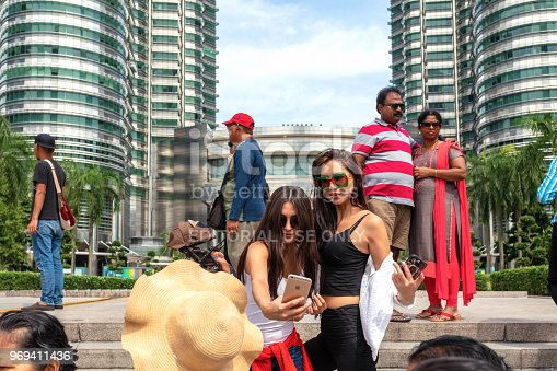 Kuala Lumpur, Malaysia - April 24, 2018: Tourists posing for photos in front of Kuala Lumpur's most popular attraction, the Petronas Towers.
