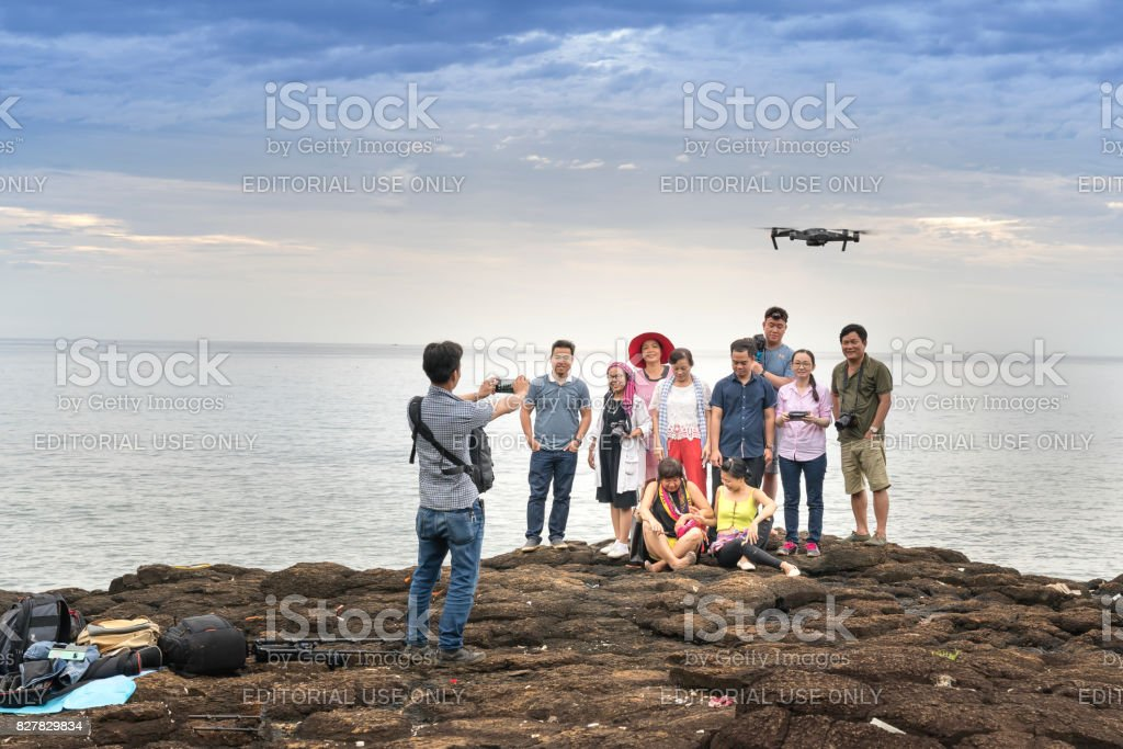Tourists posing for souvenir photography next to the coral rock stock photo