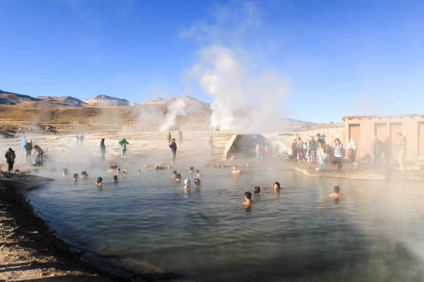 Tourists relax in natural pool of hot water in the Atacama Desert, Chile. stock photo