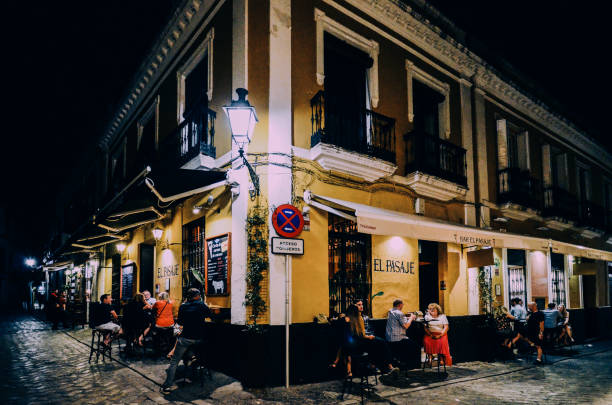 Tourists relaxing at terraces of traditional tapas bars at during in the historic centre of Seville, Andalusia, Spain stock photo