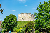 Tourists relaxing in front of Clifford's Tower in York, England