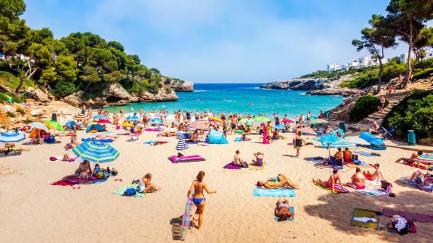 turister koppla av på cala esmeralda beach, santanyi, mallorca - golf sommar skugga bildbanksfoton och bilder
