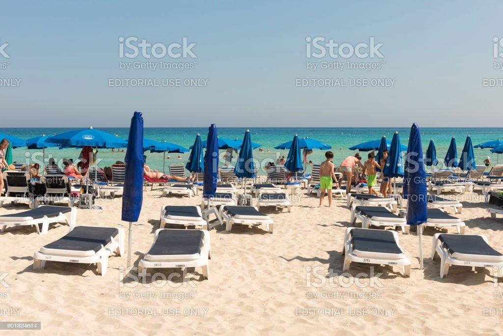 Tourists relaxing on sunbeds on a sandy beach under beach umbrellas stock photo