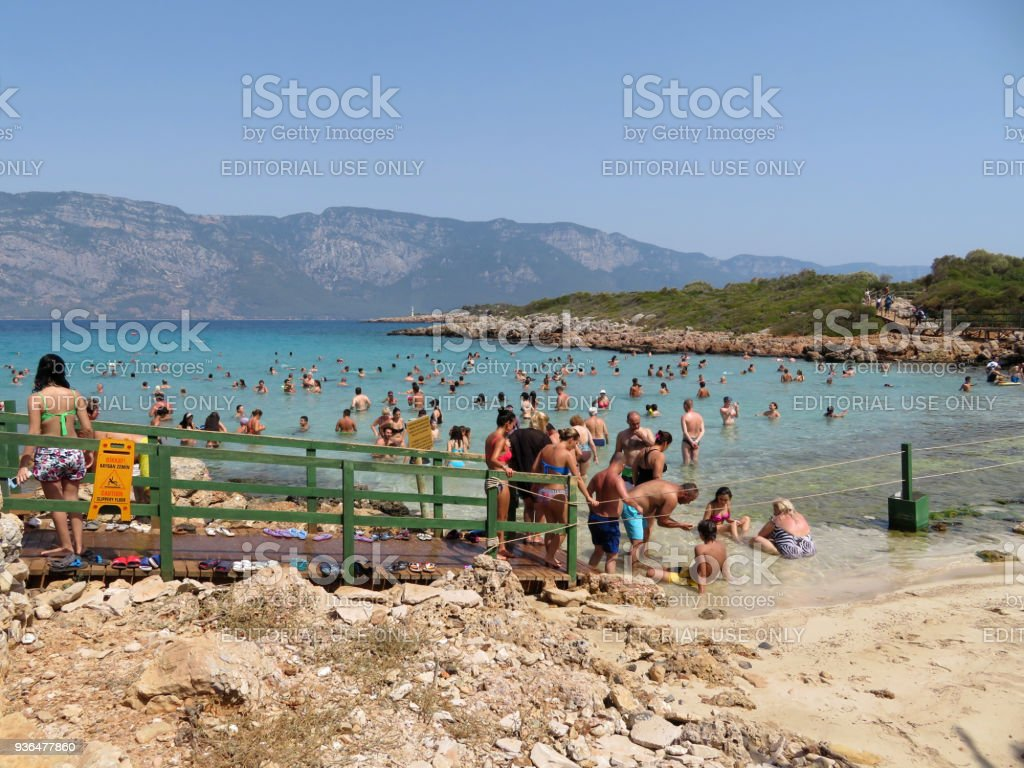 Tourists relaxing on the beach of Cleopatra island (Sedir Island) in the Aegean sea stock photo