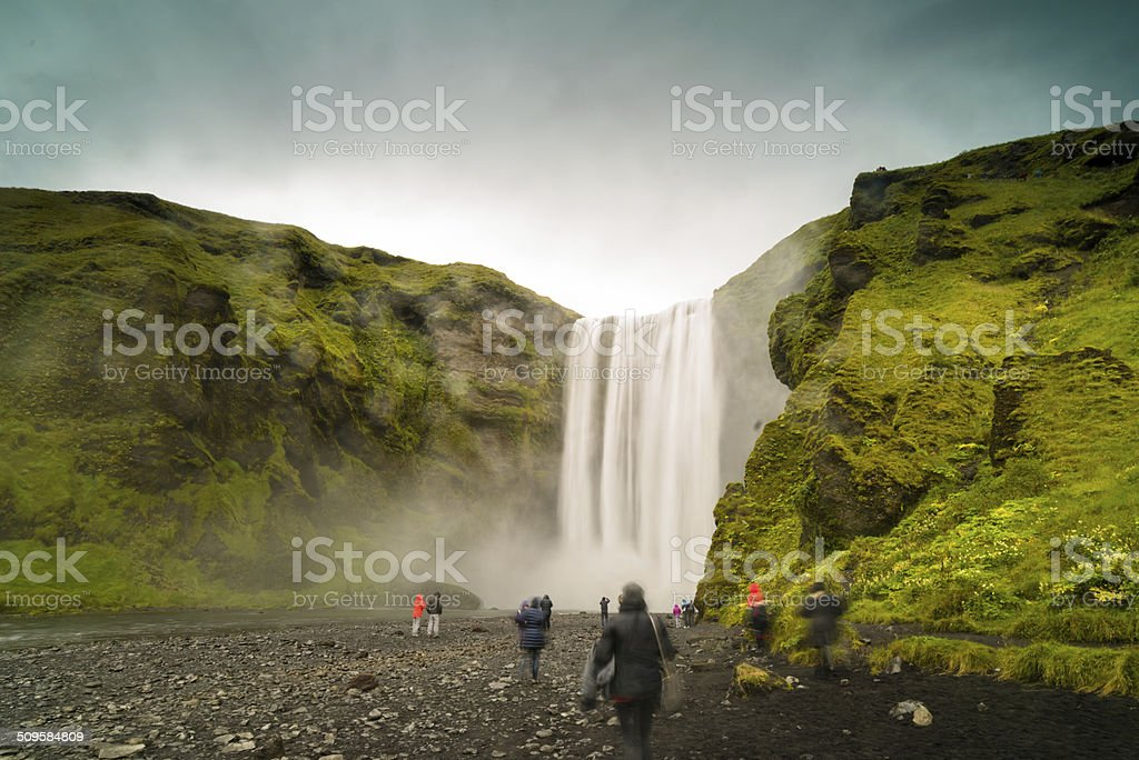 Tourists relaxing under the waterfall stock photo