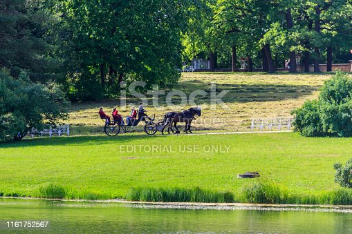 Pushkin, Russia - June 28, 2019: Tourists ride a horse-drawn carriage in Catherine park at Tsarskoe Selo in Pushkin, Russia