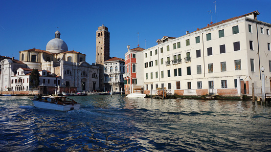 Venice, Italy- Jan 1, 2015: Tourists ride on boat under the Rialto bridge in Venice, Italy. Rialto Bridge is one of the four bridges spanning the Grand Canal in Venice